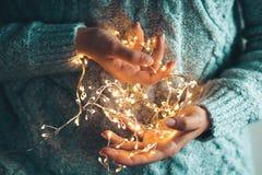 Luces en las palmas Las manos de las mujeres que sostienen una guirnalda Muchacha en un suéter azul con las luces de la Navidad e imagenes de archivo