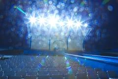 Luces en los soportes con pequeña noche del estadio de las sillas, sitios vacíos Fotografía de archivo