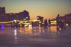 Luces falta de definición, puesta del sol y peatón de la tarde de la vida de ciudad Foto de archivo libre de regalías