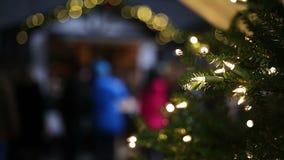 Luces que chispean en árbol adornado del Año Nuevo en el comercio justo de Navidad, humor festivo almacen de video