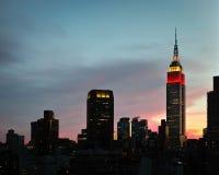 Luces rojas, blancas y azules en Empire State Building con cerca foto de archivo