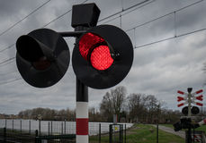 Luces rojas que centellan en la travesía de ferrocarril Fotos de archivo libres de regalías