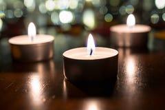 3 luces románticas del té para la cena en la tabla de madera con Bokeh en la noche Imagenes de archivo
