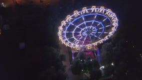 Luces tiradas aéreas de la ciudad de la noche del parque de atracciones clip Frente móvil de la visión aérea de la noria hermosa  metrajes