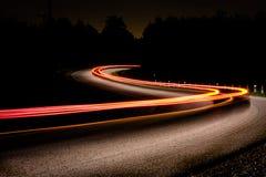 Luces traseras del automóvil en una carretera nacional oscura imagen de archivo libre de regalías