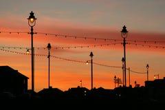 Luces y edificios contra el cielo rojo después de la puesta del sol. Fotografía de archivo libre de regalías
