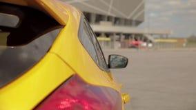 Luces y espejo retrovisor autos posteriores en el coche amarillo-naranja en el estacionamiento, neumáticos discretos de los depor almacen de metraje de vídeo