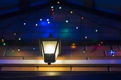 Luces y lámpara coloridas de la Navidad que brillan intensamente en la entrada de la casa Fotos de archivo libres de regalías