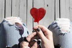 Lucette en forme de coeur rouge dans des mains à la mode du ` un s de femme à la mode, vue supérieure Image stock