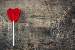Lucette rouge avec la forme de coeur sur le fond en bois Photographie stock