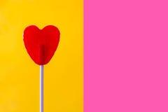 Lucette rouge avec la forme de coeur sur le fond jaune et rose Photographie stock