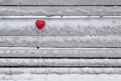Lucette rouge en forme de coeur sur le banc Image stock