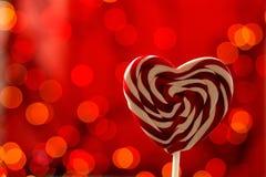 Lucette sur un bâton en forme de coeur sur un fond rouge Bokeh Photos stock
