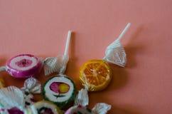 Lucettes colorées de fruit sur un fond rose, malsain mais le del Photo libre de droits