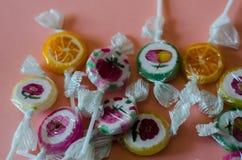 Lucettes colorées de fruit sur un fond rose, malsain mais le del Photos stock