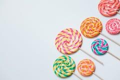 Lucettes colorées sur des bâtons sur la table blanche Sucrerie douce de caramel Photographie stock libre de droits