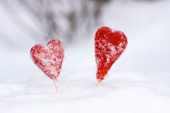 Lucettes rouges de forme de coeur dans la neige Photo stock