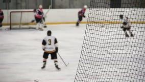 Lucha afilada entre los jugadores de equipo rivales cerca de la red durante partido importante del hockey sobre hielo almacen de metraje de vídeo