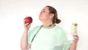 Lucha corpulenta de la mujer para comer sano almacen de metraje de vídeo