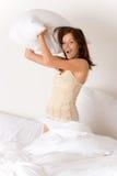 Lucha de almohadilla - mujer joven en cama Foto de archivo libre de regalías