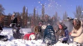 Lucha de la bola de nieve del campus de los estudiantes universitarios en el día de invierno soleado almacen de metraje de vídeo