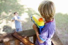 Lucha de la pistola de agua de And Son Having del padre en casa en el árbol Foto de archivo libre de regalías