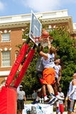 Lucha de los hombres para la bola sobre Rim In Street Basketball Tournament Imagenes de archivo