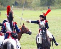 Lucha de los soldados-reenactors en caballos de montar a caballo de las espadas Imagen de archivo