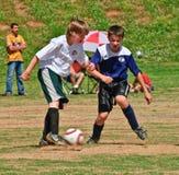 Lucha del fútbol de los muchachos para la bola Imágenes de archivo libres de regalías