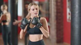 Lucha feliz de la caja del entrenamiento de la mujer con el instructor personal en gimnasio junto almacen de video