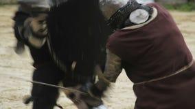 Lucha feroz de la espada, dos hombres fuertes que muestran sus habilidades marciales en campo de batalla metrajes