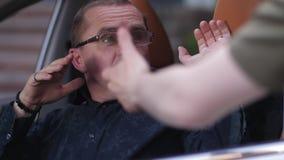 Lucha masculina del conductor apagado criminal con el arma en coche almacen de metraje de vídeo