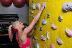 Lucha para alcanzar la toma en la pared que sube Imagen de archivo