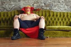 Luchador mexicano que se sienta en un sofá Fotos de archivo libres de regalías