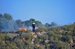 Luchar un fuego de Bush con un extintor fotos de archivo libres de regalías