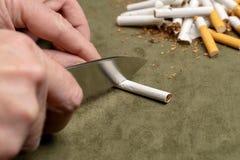 Luchar un mún hábito Un hombre corta un cigarrillo con un cuchillo en el fondo de una pila de cigarrillos quebrados fotos de archivo libres de regalías