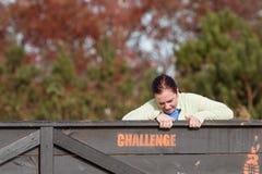 Luchas de la mujer que se tiran sobre la pared en la raza de la carrera de obstáculos Fotografía de archivo libre de regalías