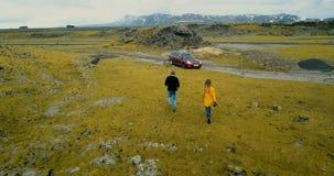 Lucht achtermening van jong paar die door vulkanisch lavagebied lopen Modieuze man en vrouw die door auto samen reizen stock footage