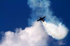 Lucht acrobatiekvliegtuig in de rookwolk Stock Afbeeldingen