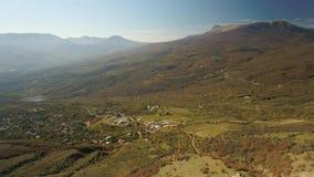 Lucht alpien landschap van een klein dorp in bergen met blauwe hemel en de herfst geel gras schot De kleurrijke herfst stock videobeelden