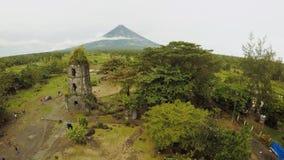 Lucht de kerkruïnes van meningscagsawa met de vulkaan van Onderstelmayon op de achtergrond, Legazpi, Filippijnen bewolking stock video