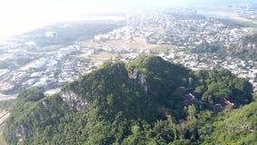 Lucht groene heuvel met tempel tegen moderne stad stock videobeelden