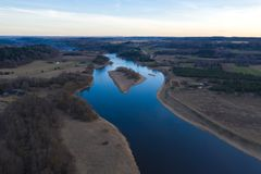 Lucht hoogste mening, het panorama van de plattelandslente van klein eiland in stille rivier op zonnige avonddag stock fotografie