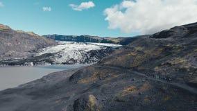 Lucht hoogste mening van de randen van witte gletsjer met een meer Toneelijsberg in nationaal park in IJsland stock footage