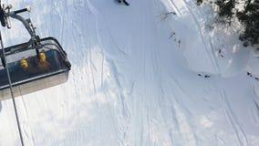 Lucht hoogste mening van een bewegende kabelbaan met mensen die daarin op sneeuwhellingsachtergrond zitten lengte Kabelwagen in s royalty-vrije stock foto