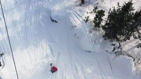 Lucht hoogste mening van een snowboarder die van zeer berijden snelle de heuvel van de poedersneeuw en neer vallen lengte Mensenp stock video