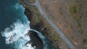 Lucht hoogste mening van oceaangolven die op donkere rotsen op zwart zandstrand breken, Canarische Eilanden, Tenerife, Spanje stock video