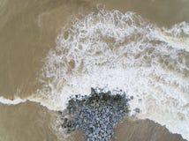Lucht hoogste mening van overzeese golven die rotsen op het strand in Pantai-bulan cahaya raken royalty-vrije stock fotografie