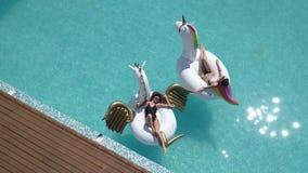 Lucht - jonge vrouwen die op luchtmatrassen de eenhoorn en Pegasus zonnebaden Aantrekkelijke jonge meisjesrust op zonnig stock video