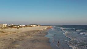 Lucht4k-lengte van mensen die en op Anastasia Island in Heilige Augustine, Florida lopen aanstoten stock video
